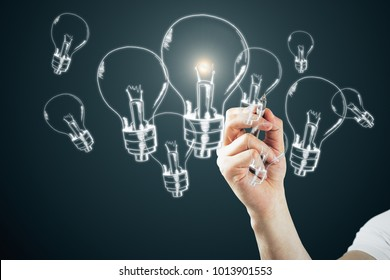 Male hand drawing glowing lamps on dark bakcground. Idea, innovation and solution concept
