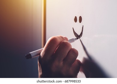 Male hand drawing smiley emoticon on office whiteboard, happy satisfied businessman during business results presentation, selective focus