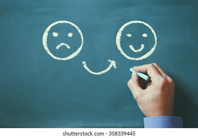 male hand drawing unhappy and happy smileys faces on chalkboard