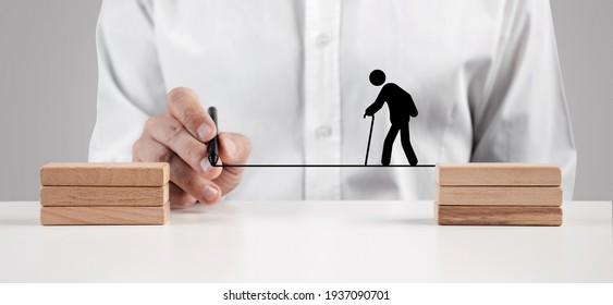 Male hand draws a line between the wooden blocks for an elder person icon with a cane to walk across. Security, support, insurance or care for senior people concept.