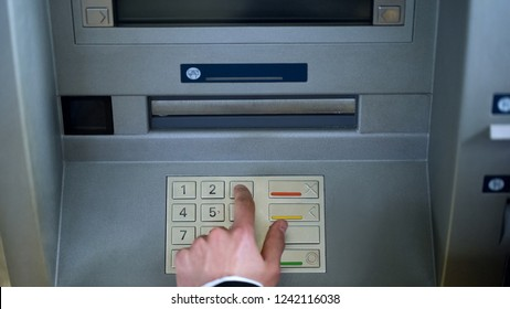 Male hand entering pin code on ATM and withdrawing euro money cash, top view