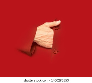 A male hand gets into the suit as Bonaparte Napoleon used to. Isolated hand on red bacground. The hand of a strategist. Conceptual image design.