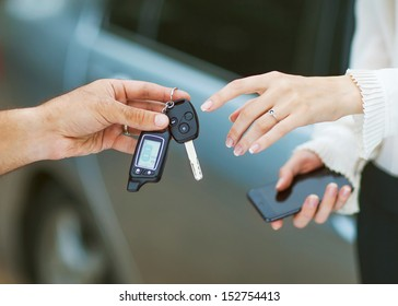 Male hand giving car key to female hand. She is holding a cell phone. In the background, a fragment of the car.