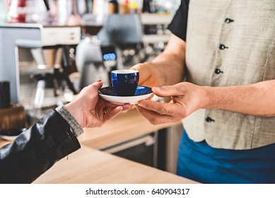 Male hand giving cup of delicious coffee to client