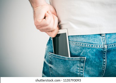 Male Hand Grabbing A Smartphone In The Left Back Pocket Of A Jeans Trouser