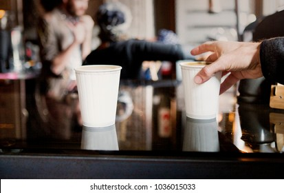 A male hand grabs a take away coffee from a counter in a coffee shop
