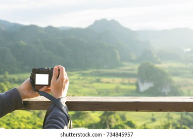 Male hand grap the camera shooting beautiful mountain scenery with sun light.