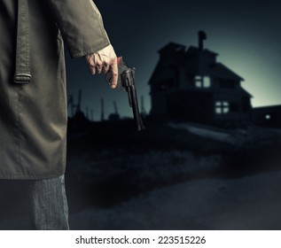 Male Hand with gun (revolver) outdoor.  Man killer looking on night house