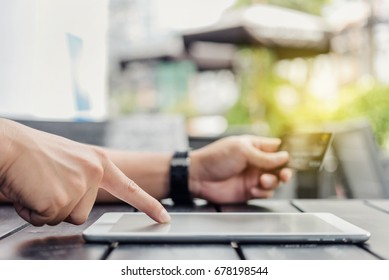 Male hand hands holding a credit card and using tablet.