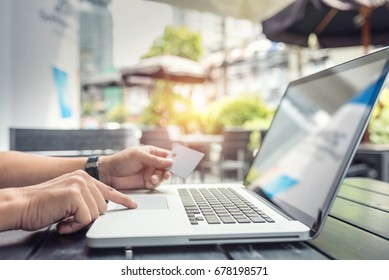 Male hand hands holding a credit card and using laptop computer.