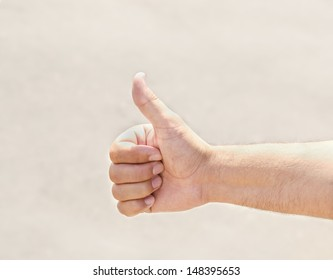 Male hand hitchhiking in sunny day