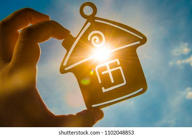 male hand hold between fingers wooden house toy against blue sunny sky with sun rays
