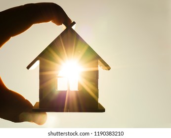 male hand hold between fingers wooden house toy agaist blue sunny sky with sun rays. solar power.