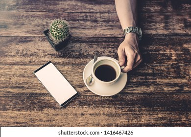 Male hand hold coffee cup with cell phone and plant on wooden table.