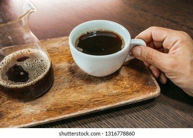 Male hand hold coffee on wood table