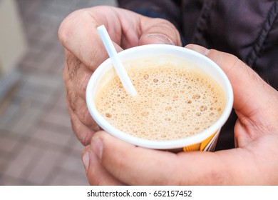 Male hand hold paper cup with coffee