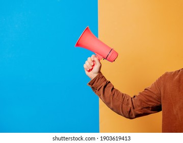 Male hand hold pink megaphone on blue and yellow backgrounds
