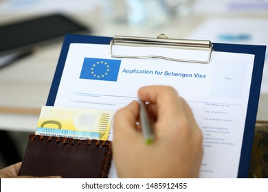 Male hand hold silver pen with passport. Filling Schengen apllication form concept