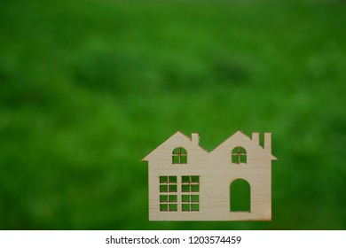 male hand hold wooden house figure against fresh green grass background.