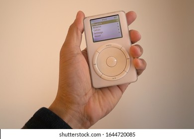 A male hand holding a 1st generation iPod with the main display turned on. Originally released October 2001. February 13, 2020. San Francisco, CA.