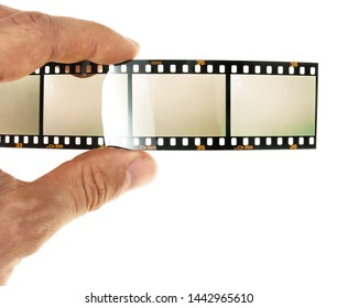 male hand holding 35mm filmstrip with empty frames or film cells, photo placeholder for your content, fingers holding film material