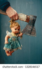 Male hand holding an ax and doll hair.