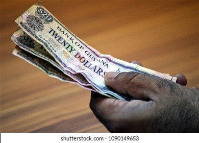 Male hand holding banknotes from Guyana, futur eldorado for major oil and gas companies. Dream becomes reality for this country.
