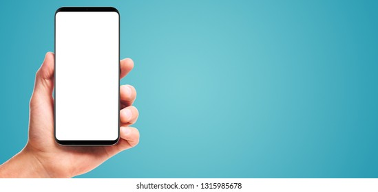 male hand holding bezel-less smartphone with blank screen, isolated on blue background . Screen is cut out with path