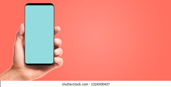 male hand holding bezel-less smartphone with blank screen, isolated on living coral background . Screen is cut out with path