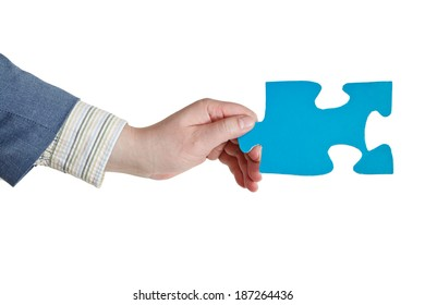 male hand holding big blue paper puzzle piece isolated on white background