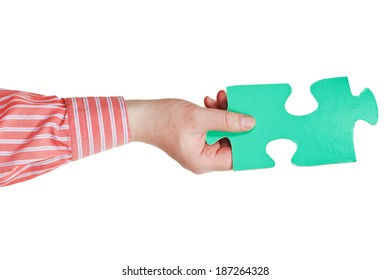 male hand holding big green paper puzzle piece isolated on white background