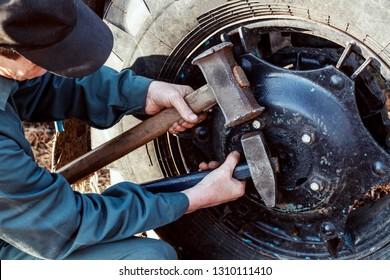 Male hand holding big hammer, sledgehammer. Mechanic repairing wheel tractor.