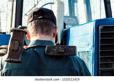 Male hand holding big hammer, sledgehammer. Repairing tractor engine.