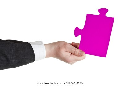 male hand holding big pink paper puzzle piece isolated on white background