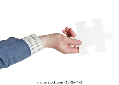 male hand holding big white paper puzzle piece isolated on white background