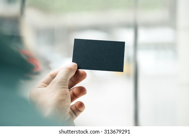 Male hand holding black business card on the window background