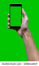 Male hand holding black cellphone with green screen at isolated green background.