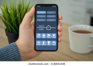 Male hand holding black touch phone with app smart home on screen in room