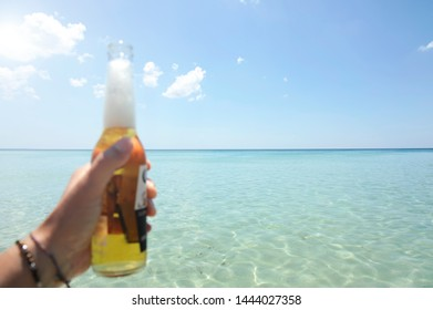 Male hand holding a bottle of beer against a sunny sky and crystal clear sea. Vacation concept.