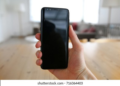 A male hand holding a brand new, very modern, state of the art mobile phone. The touch screen is black with reflections on it. An image on an interior design background with a visible wood table.
