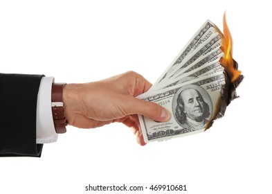 Male hand holding burning dollar banknotes on white background.