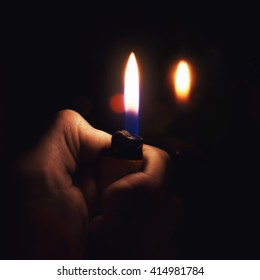 Male hand holding a burning lighter in the dark