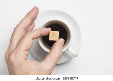 Male hand holding cane sugar cube over cup of black coffee against white background with space for text, top view, focus on sugar