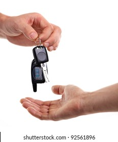 Male hand holding a car key and handing it over to another person.