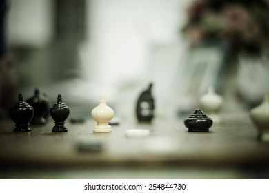 Male hand holding chess pawn, about to begin the game