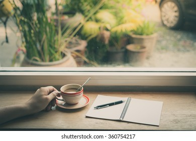 Male hand holding coffee cup on wood bar beside window at cafe in morning time with film filter effect