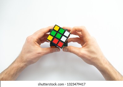 Male hand holding colorful Rubik's cubes on white background. Rubik's Cube was invented in 1974 by Hungarian sculptor and professor Erno Rubik. Concept of idea and puzzle construction.