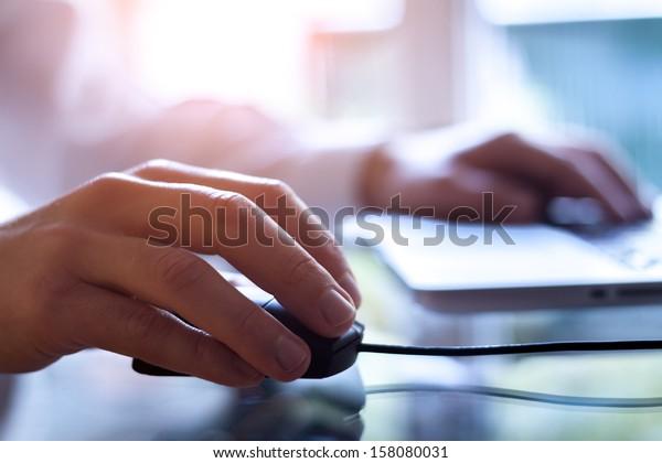 Männliche Hand, die eine Computermaus mit Laptop-Tastatur im Hintergrund hält