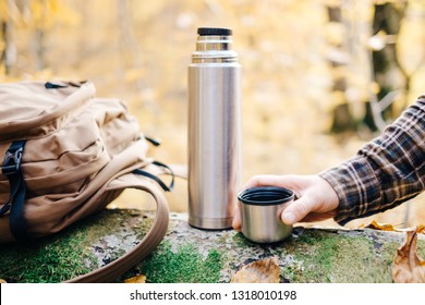 Male hand holding cup near the thermos and backpack in autumn forest.