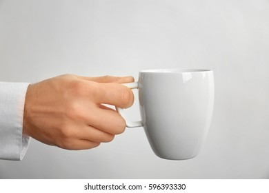 Male hand holding cup on white background